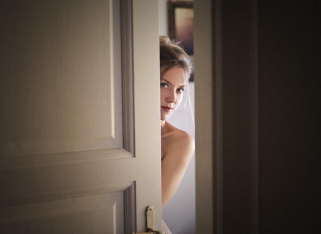 Pootvorené dvere, žena stojí za dverami