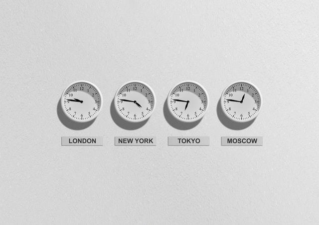 Biele hodinky na stene s časmi v Tokiu, New Yourku, Moskve a Londýne