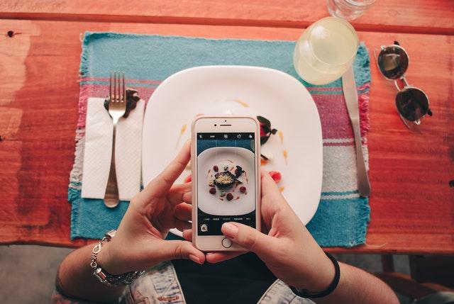 Človek si na mobil fotí jedlo na tanieri