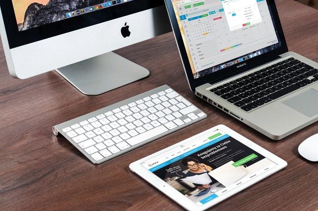 Stôl na ktorom je počítač, notebook, tablet a klávesnica.jpg