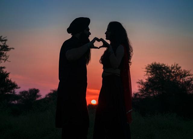 Muž a žena sa držia za ruky, stoja oproti sebe na skale pri západe slnka.jpg