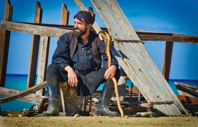 Muž s bradou sedí na škatuli pri zrúcanom plote.jpg