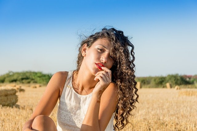 Žena s kučeravými vlasmi, v bielom tričku sedí na poli a hryzie si do prstu.jpg