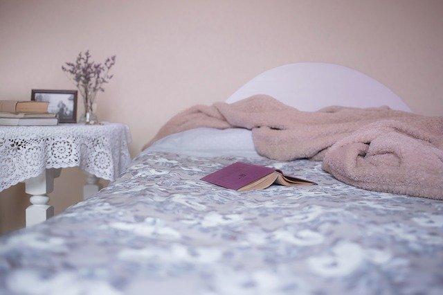 Posteľ zakrytá dekou, na ktorej je položená ružová kniha.jpg