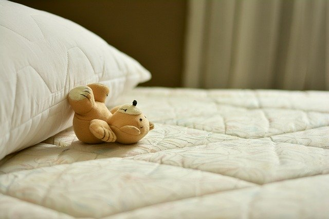 Odkrytý matrac s vankúšom a plyšovým medveďom.jpg